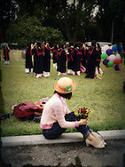 A woman looks back at a group of friends gathering for a graduation photo shooting, Hanoi, Vietnam, Southeast Asia