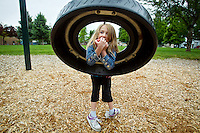 Jade Miller, 6, enjoys an apple while resting on a tire swing during an outing Friday with her family to G.O. Phippeny Park in Coeur d'Alene.