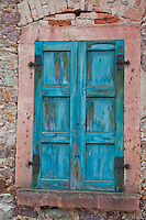 Lovely, old, weathered, blue wooden shutters in a brick house in Kohren-Salis, Germany.