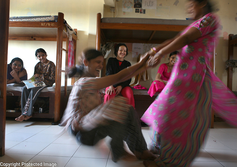 "Young girls enjoy a spinning game in their hostel at the Rescue Foundation, a non-governmental organization founded to rescue young girls from brothels in and around Mumbai, India.  The Rescue Foundation houses over 50 rescued girls at a time and some of them are Devadasis from the nearby ""Devadasi belt"" in Northern Karnataka. Most are under the age of 18 . Many of the girls suffer from some form of post-traumatic stress syndrome.  One girl doesn't speak while another tried to commit suicide by setting herself on fire while still at a brothel."
