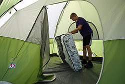March 28, 2020, Tampa, Florida, USA: 14 year old JACOB ROGERS unrolls a brand new mattress to be used in one of the tents. The city of Tampa along with Catholic Charities have set up an area that would house 100 homeless residents of Hillsborough County complete with a bed, food, toiletries and laundry facilities pictured on Saturday, March 28, 2020 in Tampa. (Credit Image: © Luis Santana/Tampa Bay Times via ZUMA Wire)
