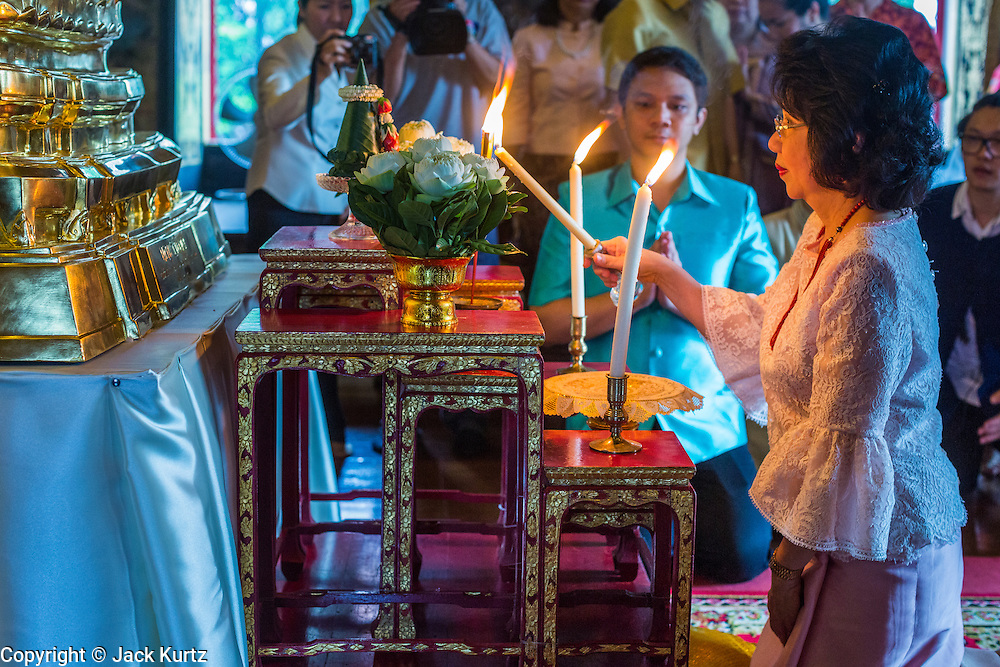 12 APRIL 2014 - BANGKOK, THAILAND: A woman lights a candle and offers a prayer before the procession for the Phra Buddha Sihing at the start of Songkran in Bangkok. The Phra Buddha Sihing, a revered statue of the Buddha, is carried by truck through the streets of Bangkok so people can make offerings and bathe it in scented oils. Songkran is celebrated in Thailand as the traditional New Year's from 13 to 16 April. The date of the festival was originally set by astrological calculation, but it is now fixed. The traditional Thai New Year has been a national holiday since 1940, when Thailand moved the first day of the year to January 1. The first day of the holiday period is generally the most devout and many people go to temples to make merit and offer prayers for the new year.    PHOTO BY JACK KURTZ