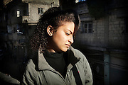 """December 8 , 2012 , Damascus , Syria : Sulaf Shahen- 16- school student , stands  on her balcony's house . Sulaf survived from a car explosion was parked under her house .  On Thursday evening December 6 , 2012 a car exploded in Mazzeh 86 area at al madaress street ( a civilian neighborhood ) and caused the death of three and many other injured .. Sulaf recounts her experience """" I had a private Mathematics lesson at my teacher's house in our neighborhood. I was supposed to attend the lesson but I was delayed for a few minutes before leaving my house. Just seconds before I was about to open the door of the house. Boom ? There was a huge explosion that pushed me back ? I flew into the air and I fell on the ground.For a moment, I lost my hearing and all feeling. Shortly after, I began to feel better and regained full consciousness. I just wanted to see what had happened. I went out to see from the balcony in our house. I saw a car divided in half and burning under our house ... it was the car that had exploded! I thought that if I had not been late for three minutes, I would have been counted with the dead."""""""