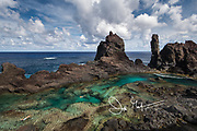 Swimmers enjoy swimming in St. Paul's Pool, a natural pool found along the coast of the volcanic landscape of Pitcairn island.