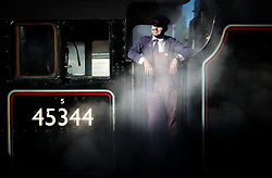 © Licensed to London News Pictures. <br /> 01/10/2016. <br /> Grosmont, UK.  <br /> <br /> The engineer of a 'Black Five' class steam locomotive looks out over the platform as steam rises up during the North Yorkshire Moors Railway Autumn Steam Weekend. <br /> The hugely popular railway line runs a service between Pickering and Whitby through the picturesque North yorkshire countryside and attracts thousands of visitors each year. <br /> <br /> Photo credit: Ian Forsyth/LNP