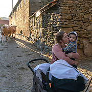Elias Coelho  (right), chats with a neighbor and ger son in the streets of Vilarinho Seco as a group of cows arrive from the fields