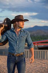 cowboy at sunset holding a saddle