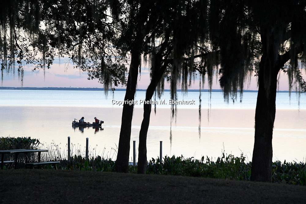 Fishermen are silhouetted as the sun sets on Lake Apopka next to Magnolia Park, Monday, Jan. 16, 2017, in Apopka, Fla. (Photo by Phelan M. Ebenhack)