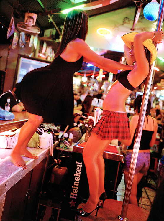 Two bar staff dance around a bar's go-go pole.