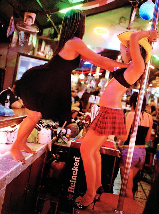 Two bar staff dance around a bar's go-go pole.