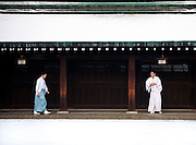 Priests rub their hands as they walk through the grounds  of Meiji Jingu Shrine after the year's first snowfall in Tokyo, Japan on 02 Feb. 2010.