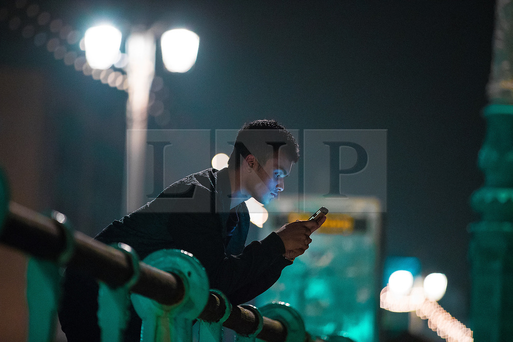 © Licensed to London News Pictures . 26/09/2017. Brighton, UK. A man using his mobile phone as he leans on railings on Brighton Promenade . Revellers at the end of a night out in Brighton during Freshers week , when university students traditionally enjoy the bars and clubs during their first nights out in a new city . Photo credit: Joel Goodman/LNP