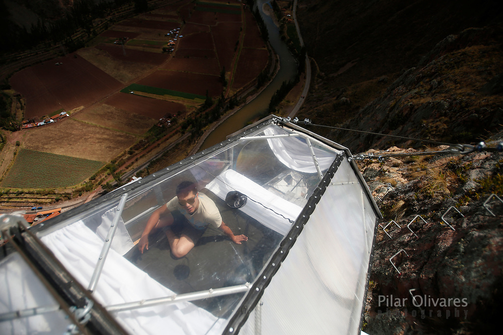 "A guide rests as he cleans the sleeping pod at the Skylodge Adventure Suites in the Sacred Valley in Cuzco, Peru, August 14, 2015. Tourists taking on an arduous climb up the steep cliff face of Peru's Sacred Valley are being rewarded for their efforts by being able to spend the night in transparent mountaintop sleeping pods at the ""Skylodge Adventure Suites"". To reach the pods, visitors need to climb 400 metres of via ferrata (a steel cable and rungs) up the valley side or hike an intrepid trail through zip lines. REUTERS/Pilar Olivares"
