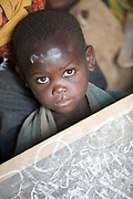 Poverty and ostracization denies Batwa children access to government-run schools. This boy attends a school funded by a Human Rights organization within his Rwamahano settlement.