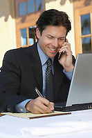Mid adult business man writing while talking on phone outdoors