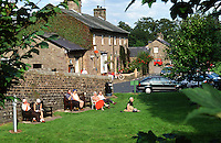 tourists relaxing in the sun on village green. England