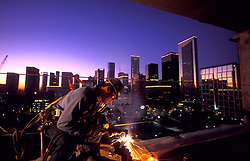 Stock photo of a welder working on the New International Hilton in Houston, Texas with the downtown skyline