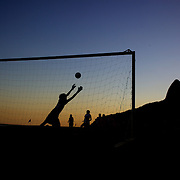Locals play football during the late afternoon sunset on Ipanema beach, Rio de Janeiro,  Brazil. 7th July 2010. Photo Tim Clayton..