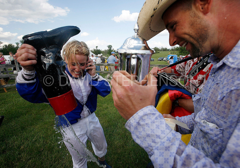 Jessica Oldham Stith poured water out of her riding boot after being dunked in a water trough along with her husband, Kevin Stith, right, after she beat seven other graduating members of the North American Racing Academy (NARA) in their first race, held in conjunction with the High Hope Steeplechase at the Kentucky Horse Park in Lexington, Ky., on Sunday, May 18, 2008. Photo by David Stephenson | Staff 5766