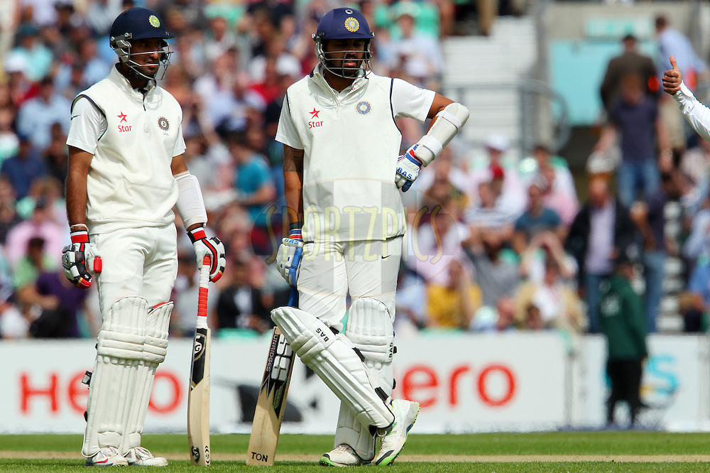 Cheteshwar Pujara of India and Murali Vijay of India look on as the umpire signals the delivery was good and Cheteshwar Pujara of India is outduring day one of the fifth Investec Test Match between England and India held at The Kia Oval cricket ground in London, England on the 15th August 2014<br /> <br /> Photo by Ron Gaunt / SPORTZPICS/ BCCI