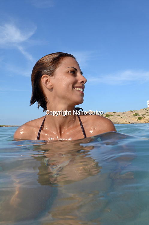 Young smiling woman enjoys the Mediterranean Sea