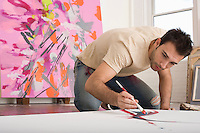 Artist Working on Canvas on Floor of Studio