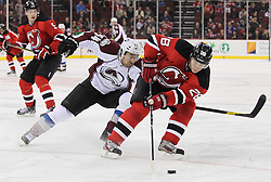 Mar 15; Newark, NJ, USA; New Jersey Devils defenseman Anton Volchenkov (28) skates with the puck while being defended by Colorado Avalanche right wing David Jones (54) during the first period at the Prudential Center.