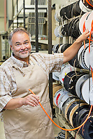 Portrait of a happy mature store clerk with electrical wire spool in hardware shop