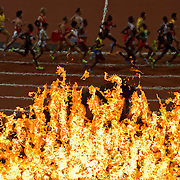 Runners in the men's 10,000m final run past the Olympic cauldron at Olympic Stadium during the 2012 Summer Olympic Games in London, England, Saturday, August 4, 2012. (David Eulitt/Kansas City Star/MCT)