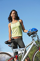 Young woman with bicycle, outdoors, portrait