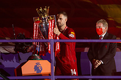 LIVERPOOL, ENGLAND - Wednesday, July 22, 2020: Liverpool's captain Jordan Henderson collects the Premier League trophy from the plinth during the trophy presentation as the Reds are crowned Champions after the FA Premier League match between Liverpool FC and Chelsea FC at Anfield. The game was played behind closed doors due to the UK government's social distancing laws during the Coronavirus COVID-19 Pandemic. (Pic by David Rawcliffe/Propaganda)