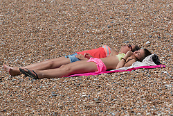 © Licensed to London News Pictures. 01/06/2014. Brighton, UK. Some woman relaxing and sunbathing on the beach. Despite a good start to the weekend on Saturday the weather has deterred some people from coming to the beach. Photo credit : Hugo Michiels/LNP