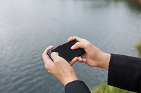 Close-up of businessman's hands texting on smart phone along river