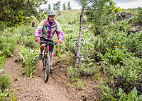 A woman mountain biking down a portion of the Buck Mountain Loop Trail outside Winthrop, Washington, USA.