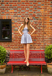Teenage Girl Standing on Red Bench