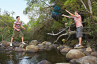 Young Man Throwing Backpack Across Creek