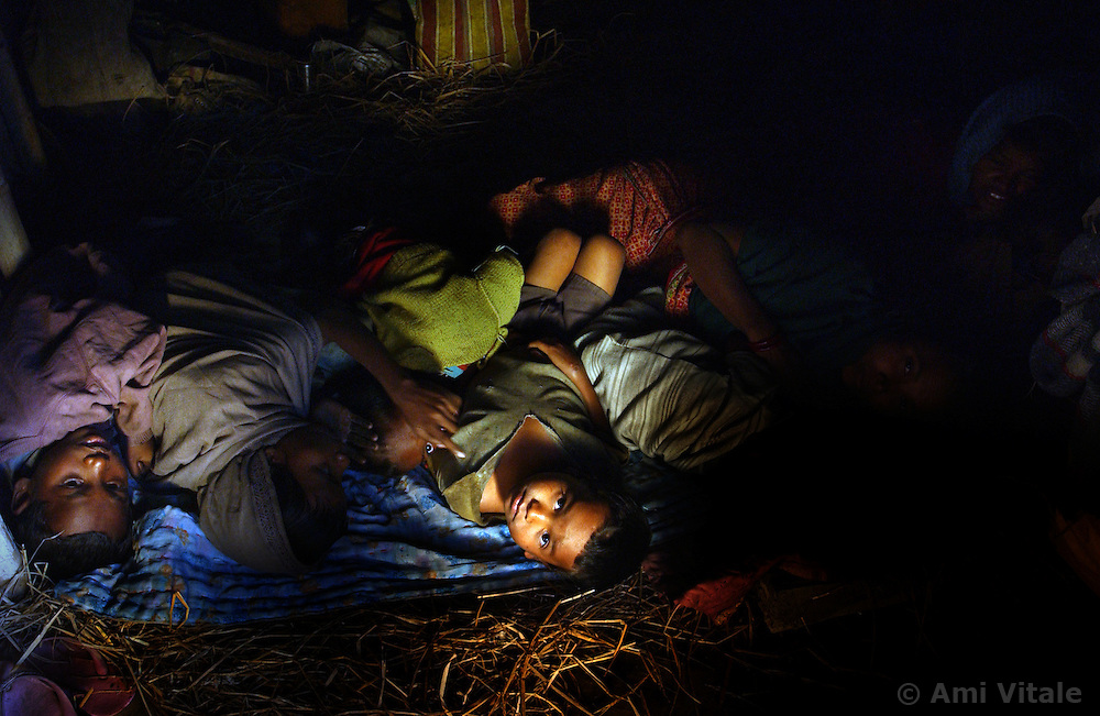 Villagers who lost their homes to elephants wake up on the floor of a neighbors house  near Tezpur in Assam, eastern India January 6, 2004.  Villagers have been forced to stay up lighting fires, banging tin cans, throwing firecrackers to keep elephants from destroying their crops, homes and somtimes killing people. India and its sacred elephants are threatened by the deforestation caused by encroachment of the reserved land and natural forests.  As a result, wild elephants are rampaging through villages, killing people and destroying their homes and crops. (Ami Vitale)