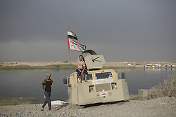 October 21, 2016 - Qayyarah, Iraqi-Kurdistan, Iraq - Iraqi Shia militia are seen with their armoured Humvee at a checkpoint on the Tigris River near the town of Qayyarah...Since being retaken from the Islamic State the town of Qayyarah has become an important staging post for the Iraqi Army, and some US support elements, in the buildup to the Mosul offensive. (Credit Image: © Matt Cetti-Roberts/London News Pictures via ZUMA Wire)
