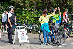 © Licensed to London News Pictures. 26/04/2020. London, UK. A Police officer speaks to two cyclists (cycling has been banned for adults) while out patrolling in Richmond Park. Members of the public go out to enjoy the warm weather in Richmond Park which looked busy today during lockdown where temperatures are expected to reach 21c. London has seen an increase in traffic and busier High Streets as more shops and cafes start to open up during the coronavirus pandemic crisis. Photo credit: Alex Lentati/LNP