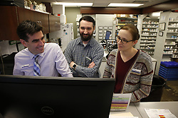 March 21, 2019 - Joliet, IL, USA - Chad Kodiak, pharmacist and owner of Joliet Professional Pharmacy, left, troubleshoots a software billing glitch with co-workers Steven Quigley and Maura Murph, on March 21, 2019, in Joliet. The pharmacy has been in Kodiak's family for 50 years. (Credit Image: © Stacey Wescott/Chicago Tribune/TNS via ZUMA Wire)