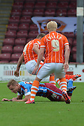 Gary McSheffrey  felled by Jim McAlister  and Mark Cullen  during the Sky Bet League 1 match between Scunthorpe United and Blackpool at Glanford Park, Scunthorpe, England on 5 September 2015. Photo by Ian Lyall.