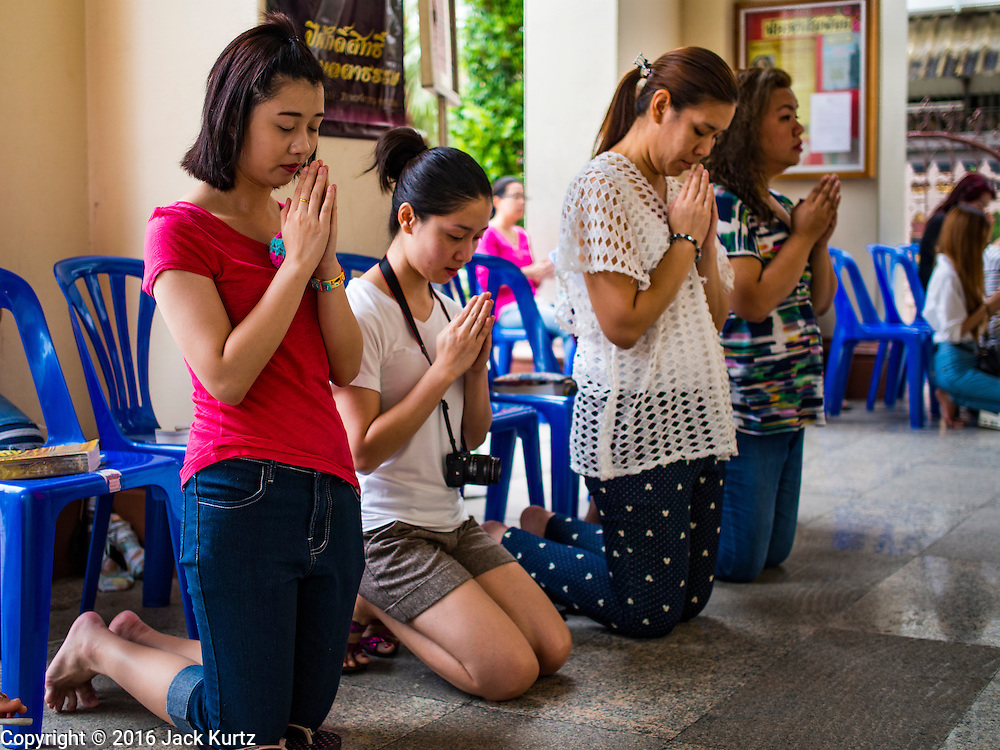 27 MARCH 2016 - BANGKOK, THAILAND: Women pray in the portico during Easter services at Santa Cruz Church in Bangkok. Santa Cruz was one of the first Catholic churches established in Bangkok. It was built in the late 1700s by Portuguese soldiers allied with King Taksin the Great in his battles against the Burmese who invaded Thailand (then Siam). There are about 300,000 Catholics in Thailand, in 10 dioceses with 436 parishes. Easter marks the resurrection of Jesus after his crucifixion and is celebrated in Christian communities around the world.      PHOTO BY JACK KURTZ