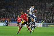 Cardiff city's Peter Odemwingie (l) is challenged by West Brom's Claudio Yacob. Barclays Premier league, Cardiff city v West Bromwich Albion at the Cardiff city Stadium in Cardiff, South Wales on Saturday 14th Dec 2013. pic by Andrew Orchard, Andrew Orchard sports photography.