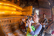 26 NOVEMBER 2012 - BANGKOK, THAILAND: Tourists take pictures in the hall housing the Reclining Buddha in Wat Pho in Bangkok. Thailand's Temple of the Reclining Buddha has gained further global prominence following a 45-minute tour by U.S. President Barack Obama and Secretary of State Hillary Clinton during their November 18-19 visit to the kingdom. Known also as the Temple of the Reclining Buddha, its official name is Wat Phra Chettuphon Wimon Mangkhlaram Ratchaworamahawihan. The temple is also known as the birthplace of traditional Thai massage. There is a popular massage school on the temple grounds.     PHOTO BY JACK KURTZ