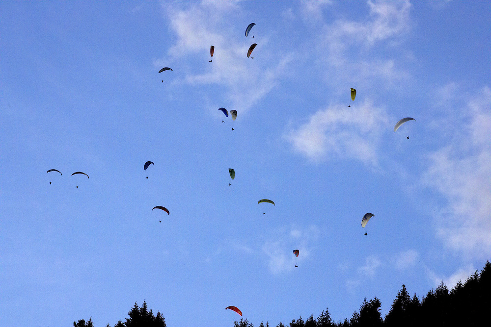 A multitude of paragliders accumulate in a late evening thermal above the skyline in Queenstown, New Zealand