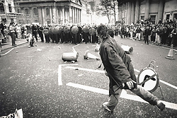 © Licensed to London News Pictures. 25/03/2020. London, UK. In this image from March 31st 1990 a protester throws an object at a line of riot police on St Martin's Place during the London poll tax riots. The protest on the last day of March in 1990 started peacefully when thousands gathered in a south London park to demonstrate against Margaret Thatcher's Government's introduction of the Community Charge - commonly known as the poll tax. Marchers walked to Whitehall and Trafalgar Square where violence broke out with the trouble spreading up through Charring Cross Road and on to the West End. Police estimated that 200,000 people had joined the protest and 339 were arrested. The hated tax was eventually replaced by the Council Tax under John Major's government in 1992.  Photo credit: Peter Macdiarmid/LNP