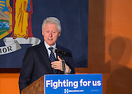 Elmont, New York, USA. April 5, 2016. Former President Bill Clinton, deliving a speech, is the headline speaker as he campaigns at an Organizing Event rally in Elmont, Long Island, on behalf of his wife, Hillary Clinton, the leading Democratic presidential candidate, and former Secretary of State and U.S. Senator for New York. Podium has 'Fighting for us' slogan on sign. The New York Democratic Primary takes place April 19th.