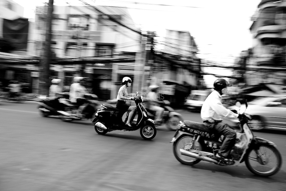 Woman drives scooter downtown in Ho Chi Minh City, Vietnam