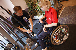 Access to services, Fitness instructor and disabled woman in the gym; using Jungle Cable,