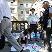A fluoride opponent confronts a fluoride supporter while China Starshine, kneeling, paints anti-fluoride signs outside City Hall. Portland, Ore., is one of the only large cities in America not adding fluoride to its water supply. The fluoridation deliberations are ongoing, and both sides of the issue are dug in.